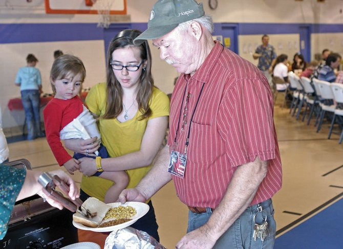 Love INC board president John Furman, right, gathers food for Patricia Vaughn and her friend's daughter, Jordyn Mannon, 2, during Sunday's fourth annual pig roast and silent auction fundraiser at the Boys & Girls Club of Craig. Love INC will use funds raised Sunday for general operating costs.