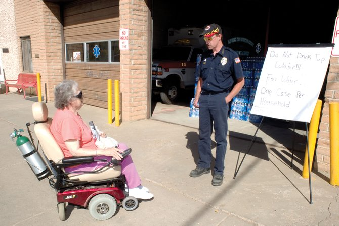 "Firefighter Dave More visits with Vi Shaffer outside the downtown Oak Creek fire station. Shaffer had made her way from the Aspen View Manor on Monday morning to the fire station to get bottled water. Oak Creek is under a ""boil water order"" after a valve broke and emptied the town's water tank."