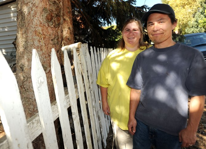 John and Tanya Taing, of Oak Creek, stand next to their white picket fence that will get a new coat of paint with the help of Routt County Habitat for Humanity. The small home repair project, called A Brush With Kindness, is looking for more volunteers for this weekend.