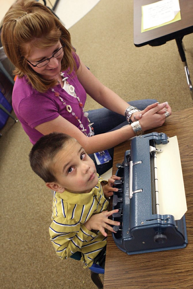 First-grader Brayden Martinez, 6, practices on his Braille typewriter with paraprofessional Shana Miles on Thursday at Sandrock Elementary School. Miles learned Braille through online classes specifically to work with Martinez.