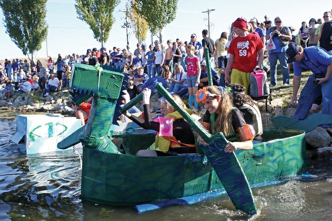 Gondor the Green Dragon, a boat made and controlled by juniors Amy Chadwick, wearing orange arm floaties, April Rogers, in pink, and Tasha Burke, in back, starts its voyage during the cardboard boat regatta Friday at Loudy-Simpson Park. Students made their boats out of corrugated cardboard, glue, tape, caulking and sealant, but could not use materials such as plastic or fiberglass.