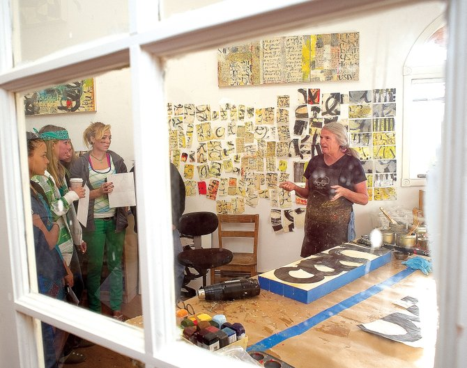 Local artist Laura Wait, seen through one of the panels of the glass door of the art studio in her downtown Steamboat Springs home, invited a group of aspiring artists from Steamboat Springs High School into her home Thursday morning as part of a field trip sponsored by the Steamboat Springs Center for Visual Arts. The field trip allowed high school students to visit the studios of local artists to see where and how the artists work.