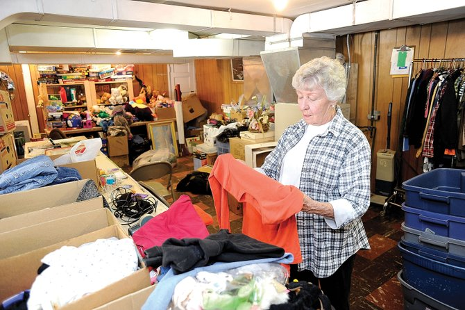 Lois Stefano sorts through clothing at the thrift store located at the Phippsburg Community Club. The store offers a wide range of used items for sale to the community, and the money raised helps take care of the town park and pays the electric bills for the light poles in town.