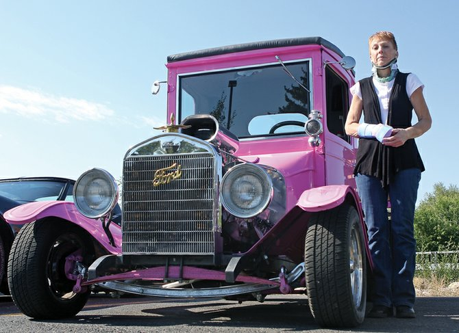Maria Ellis stands next to George and Karen Vassek's 1925 Ford Tall-T truck during a fundraiser Saturday at the OP Bar & Grill. Ellis was injured in a car accident Aug. 29 north of Baggs, Wyo. The fundraiser, which raised an estimated $2,500, was organized to help defray Ellis' medical costs.