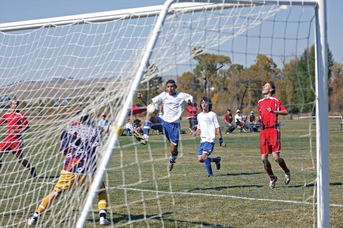 Sophomore Alex Perez volleys a shot into the goal during a game against Glenwood Springs High School on Saturday at Loudy-Simpson Park. The Bulldogs won the game, 3-1.