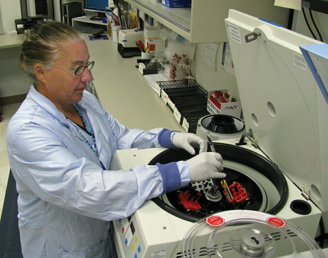Yampa Valley Medical Center lab support tech Cheryl Stene places a blood tube into the centrifuge to begin processing.