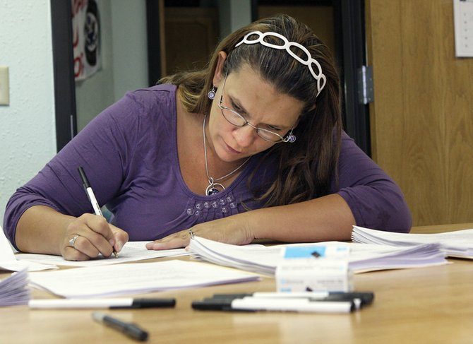 Brenda Whiteside, of Hayden, fills out paperwork as part of an application process during a job fair Tuesday at the Colorado Workforce Center of Craig. Organizers aim to fill 10 to 12 seasonal positions at Yampa Valley Regional Airport, and will be accepting applications at the center through Thursday.