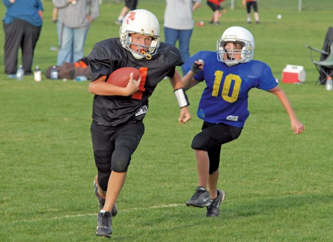 Hayden quarterback Isaac Maestas prepares to score a touchdown during his fifth- and sixth-grade Doak Walker team's Tuesday game against the Chargers. Hayden won the game, 22-14, putting them in second place overall. They will play in the Oct. 12 championship game against the undefeated Bengals.