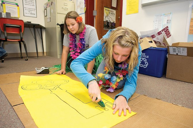 Soroco high school students Miranda Watts, front, and Brittney Romero work on making a key for Thursday afternoon's homecoming pep rally at the high school.
