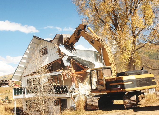 A trackhoe operated by an employee of Rogue Resources begins demolition of one of two residential buildings immediately east of Casey's Pond. The buildings are coming down to make room for the senior campus being developed cooperatively by Pearl Senior Living and Yampa Valley Medical Center on Walton Creek Road.