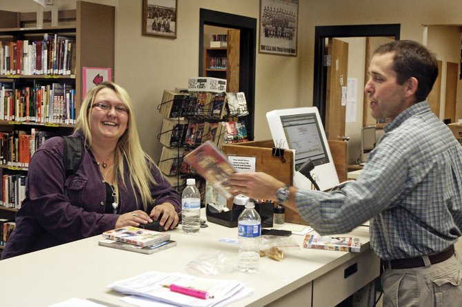 Moffat County High School librarian James Neton, right, checks out books for senior Shelise Kowach on Tuesday in the school's library. The school recently won $500 worth of literature through a raffle. The school's library houses about 17,000 books for its 600 students.