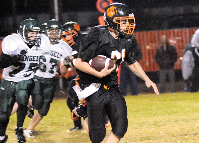 Hayden sophomore running back Ryan Domson runs from a pack of Rangely defenders Friday night. The Panthers suited up only 14 players for the game and started four freshmen. The Tigers took the advantage early, scoring 33 first-quarter points that led to a 47-14 victory.
