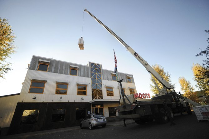 A crane is used Sept. 30 to lift solar panels onto the roof of the Moots Cycles building. The solar-panel system will save Moots about $1,500 in electricity costs annually at its 15,000-square-foot factory and office facility on Steamboat Springs' west side.