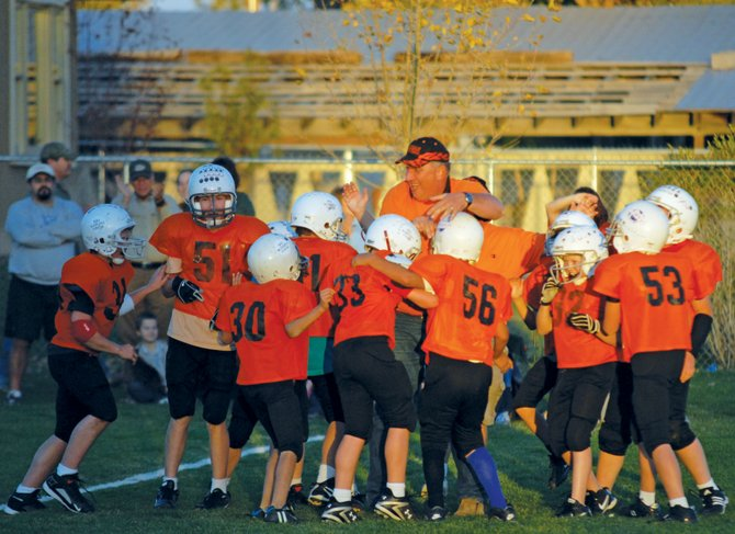Bengals coach Mark Balderston converges with his team at midfield at the end of the Tuesday championship game. The Bengals beat the Hayden Tigers, 30-12, to complete a 7-0 season in the fifth- and sixth-grade Doak Walker league.