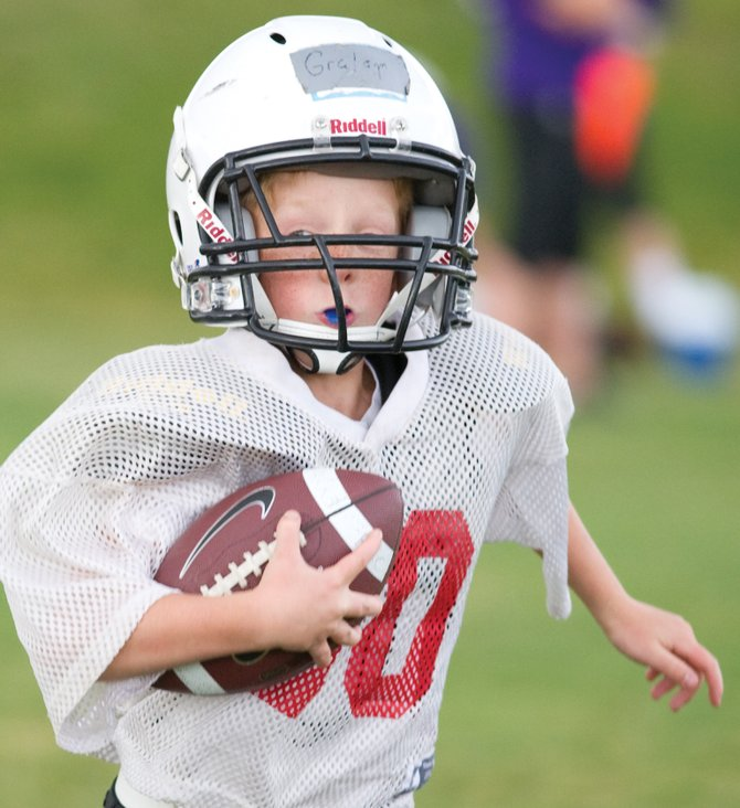 Youth football player Graham Calistro finds some running room during practice Monday at Ski Town Fields.