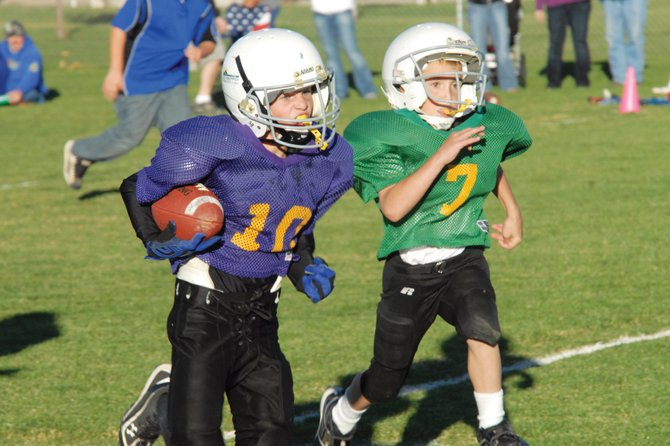 Chris Scherbarth, of Meeker, rushes for the Viking offense and heads for the goal line as Packers defender Riggen Myers tries to stop him. The Vikings beat the Packers, 18-6, to win the championship for the third- and fourth-grade age division of Doak Walker football.