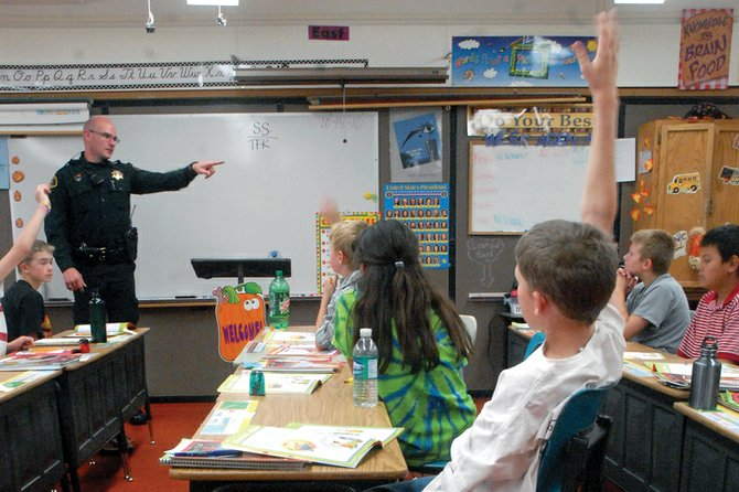 Deputy Ryan Hess, of the Moffat County Sheriff's Office, fields questions Thursday from Britni Morton's fifth-grade students during a Drug Abuse Resistance Education presentation at East Elementary School. Hess has been teaching drug awareness and prevention to area students for four years.
