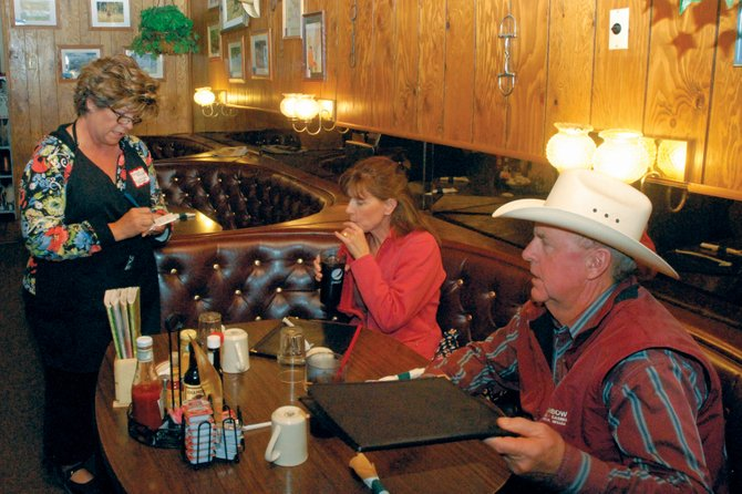 Moffat County clerk and recorder Elaine Sullivan takes the lunch orders of Kelly and Mike Nottingham on Friday afternoon at the Golden Cavvy, 538 Yampa Ave. Sullivan and numerous other volunteers waited tables at the restaurant as part of a fundraiser for Christmas for Kids.