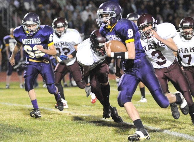 West Grand junior Travis Gore runs away from a pack of Soroco defenders Friday as the Mustangs rolled past the Rams, 46-6. 