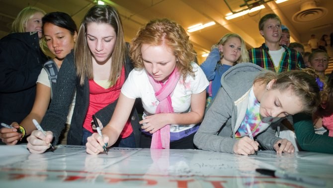 Christi Valicenti, left, Gaby Strnad, center, and Brooke Bumgarner, right, sign a banner for Rachel's Challenge. Hundreds of students at Steamboat Springs High School attended the Rachel's Challenge assembly, which explained the concept behind the school-based program that motivates students to make a positive change in the way they treat others, at the high school on Wednesday. The program is named after Columbine High School victim Rachel Scott and is designed to encompass the young woman's kindness and compassion.