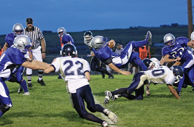 Mason Updike, a Moffat County High School junior shown here with the ball, takes a hard tackle while running up the field during the Bulldogs' game against Evergreen. The MCHS varsity teams hosts the league-leading Rifle Bears tonight.