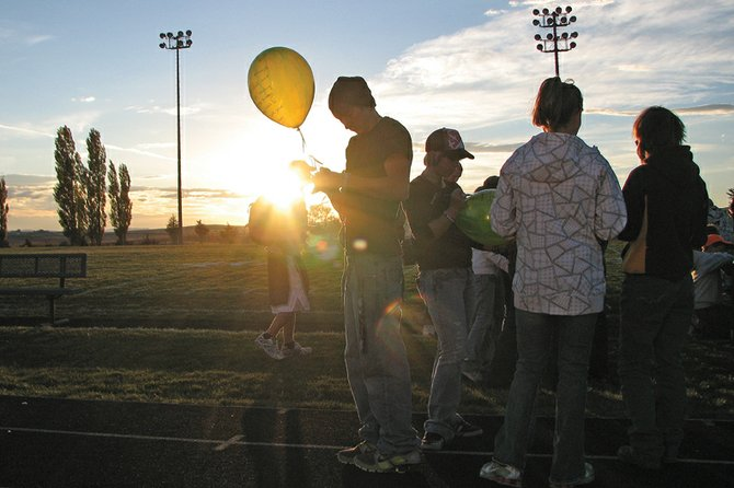 Students at Moffat County High School write notes on balloons for Russell Walsh during a balloon vigil at Thursday at the MCHS football field. Approximately 900 balloons were released in memory of Walsh, 16, who was killed in a single-vehicle crash Saturday.