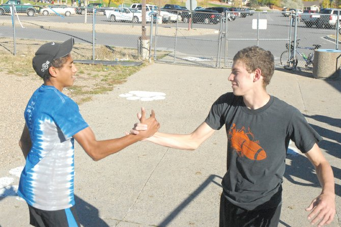 Moffat County High School cross-country runners Alfredo Lebron, left, and Chris Zirkle shake hands before warming up for a recent practice. The two have finished their last six races 1-2, with Zirkle in first and Lebron in second. They will join the rest of the MCHS team today at the regional meet hosted by Montezuma-Cortez.