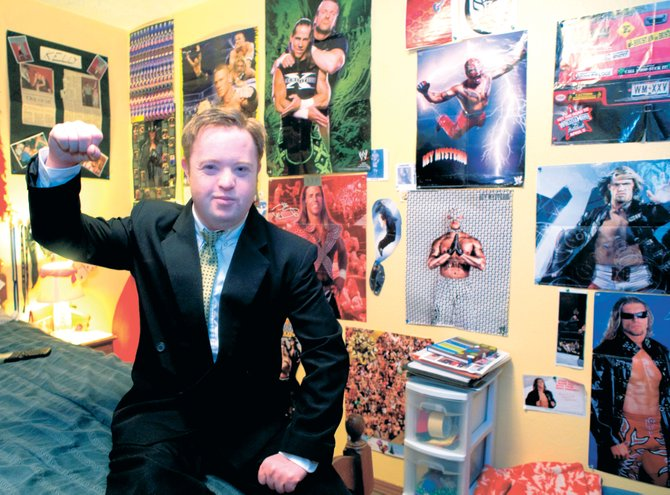 Kelly Chambers strikes a pose from one of his favorite wrestling posters inside his room. Chambers, who will celebrate his 28th birthday today, loves wrestling and has lined the walls of his room with posters of his favorite professional wrestlers and clippings from his own high school wrestling career at Steamboat Springs High School.