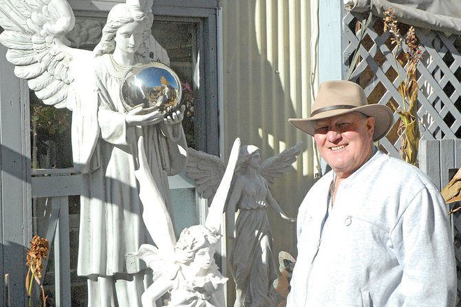 Bob Meckley stands next to a pair of angel statues at his gardening business, Tunies & Such, at 690 Yampa Ave. The statues commemorate his late wife, Sharon, and daughter, TJ. Meckley's business features numerous other lawn decorations and fountains, along with plants.