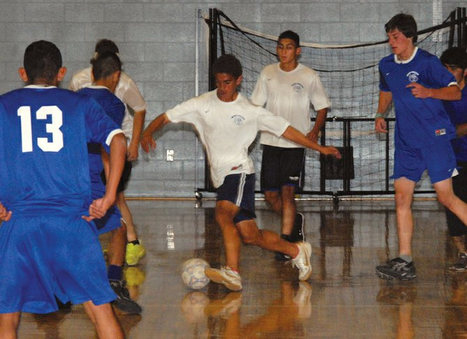 Moffat County soccer player Alan Flores handles the ball during the boys varsity team's indoor practice Monday afternoon in the MCHS gymnasium. The team qualified for the state playoffs last week and will travel Wednesday to Windsor for the first round of play.