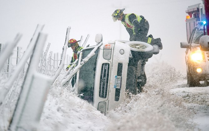 Members of Steamboat Springs Fire Rescue pull items out of an overturned Toyota sport utility vehicle on Routt County Road 129 near Elk River Estates on Monday morning. Officials said no one was injured in the accident or any of the others that resulted from Mondays wintry weather.