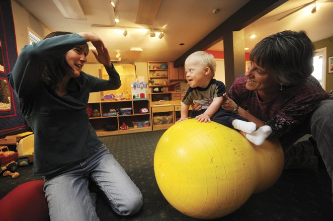 Carolyn Kleckler, left, sings a song to her 14-month-old son, Lewis, while occupational therapist Jodi Glaisher works on Lewis posture Oct. 19 at Horizons Specialized Services.
