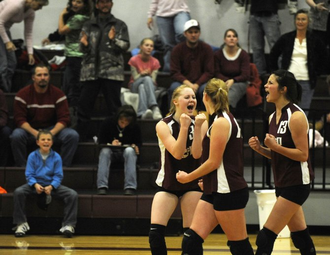 Soroco High School volleyball players, from left, Caitlyn Berry, Shelby Miles and Ceanna Rossi celebrate after scoring one of the final points during Tuesday night's match against West Grand. Soroco won their first-round playoff match, 3-2.