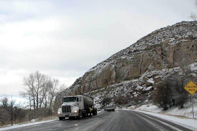 A truck driver puts chains on his tires this morning near Mount Harris on the eastbound lane of U.S. Highway 40, just east of Hayden. Earlier in the morning, the same stretch of highway had been closed for more than an hour due to a vehicle blocking both lanes. Deputy Dara Frick, of the Routt County Sheriff's Office, said the Colorado Department of Transportation had to sand the roadway to remove the stuck vehicle.