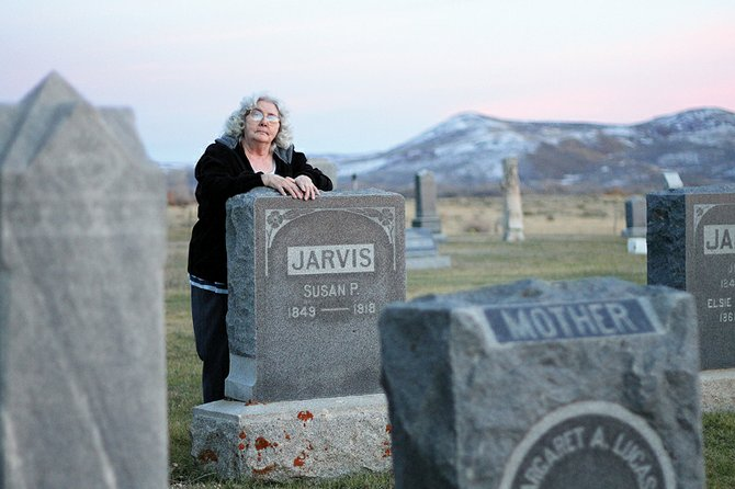 Craig resident and ghost hunter Barbara Nicholes, 71, stands Thursday night in the Craig Cemetery. Nicholes started taking photos of area cemeteries at night about six months ago. After collecting thousands of photos, she contends some of the images prove there is life after death.