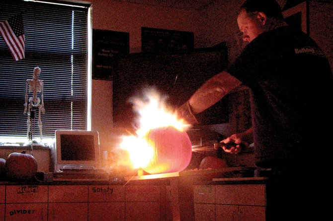 Craig Middle School science teacher Norm Yoast ignites acetylene gas within a pumpkin Friday. For five consecutive Halloweens, Yoast has been detonating pumpkins at CMS to teach principles in chemistry and physics.