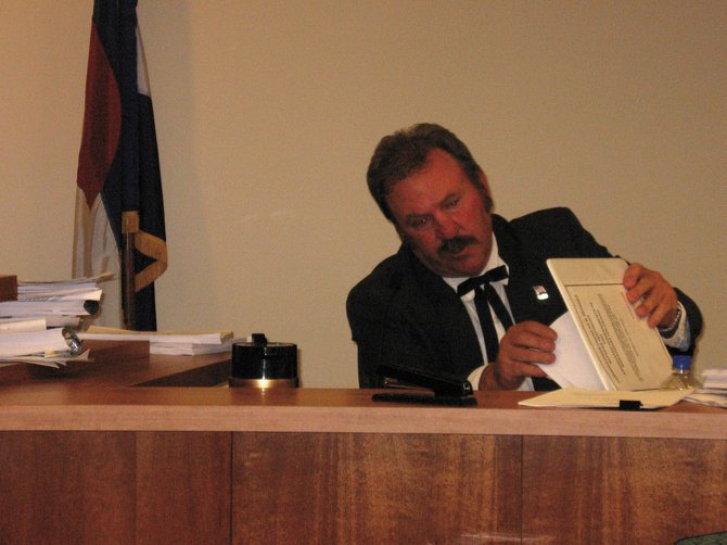 Routt County Commissioner Doug Monger checks statistics Friday while testifying in Denver before the Public Utilities Commission, which is conducting hearings about potential impacts of new state energy legislation.
