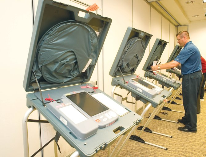 Election judge Kevin Kaminski sets up an electronic voting machine at a polling station inside the Yampa Valley Medical Center on Monday afternoon.