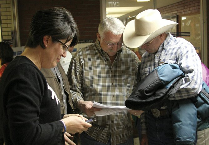 Tom Mathers, middle, looks over results with fellow Moffat County Commissioner Tom Gray while his wife, Stacey Mathers, left, checks her phone Tuesday night at the Moffat County Courthouse. Mathers, the incumbent, defeated write-in candidate Kerry Moe in the general election for Moffat County Commission, District 3.
