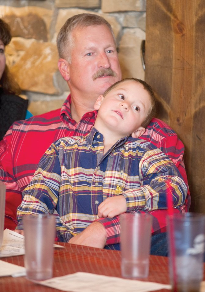 Garrett Wiggins holds his son Cody while watching election results at the Republican watch party at the Steamboat Smokehouse on Tuesday night. Wiggins defeated incumbent Routt County Sheriff Gary Wall and will take over the office in January.