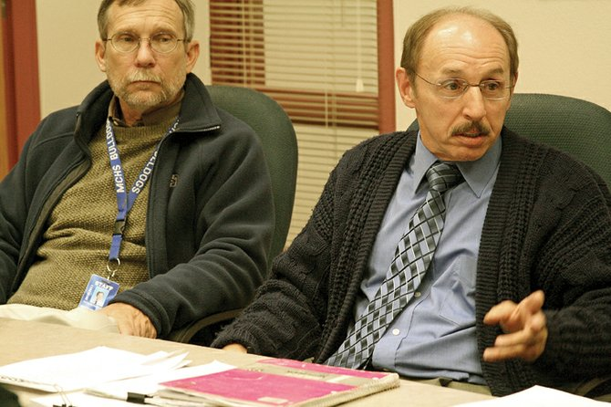 Board member Ron Schaeffer, right, makes a case for limiting the scope of the Communities Overcoming Meth Abuse group rather than disbanding it, while Thom Schnellinger looks on. The board voted 9-1 at its Wednesday meeting to dissolve the group by Dec. 31.