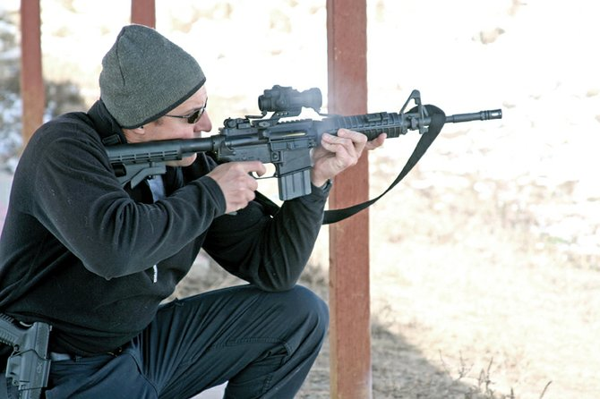 Cpl. Travis Young, of the Craig Police Department, discharges a round Wednesday at Bears Ears Sportsman Club during a shooting competition.
