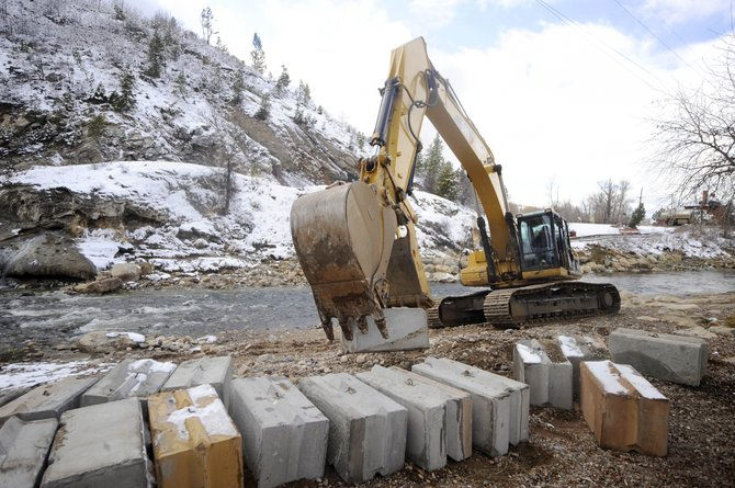 A Nordic Excavating track hoe places concrete blocks Thursday on the banks of the Yampa River that will be used to divert the river so repairs can be made to Charlie's Hole across from Bud Werner Memorial Library. Work is expected to be complete by Wednesday. Parking at the library might be temporarily affected.