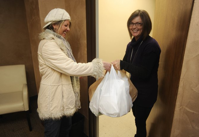 Oak Creek's Chelsea's Restaurant co-owner Jaila Benjamin, left, delivers lunches to Yampa Valley Medical Center pain management office coordinator Alison Frinks on Thursday. The Chinese restaurant is offering lunch delivery Wednesdays and Thursdays.