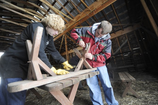 The Lowell Whiteman School seniors Will Horner, left, and David Lea repair a bench Thursday at the city-owned Legacy Ranch as part of a community service project.