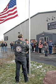 Veterans Mark Wick and Jim Meineke raise a flag during a dedication ceremony Saturday at Thunder Rolls Bowling Center in Craig. The dedication capped a month-long fundraiser for the Bowlers to Veterans Link.