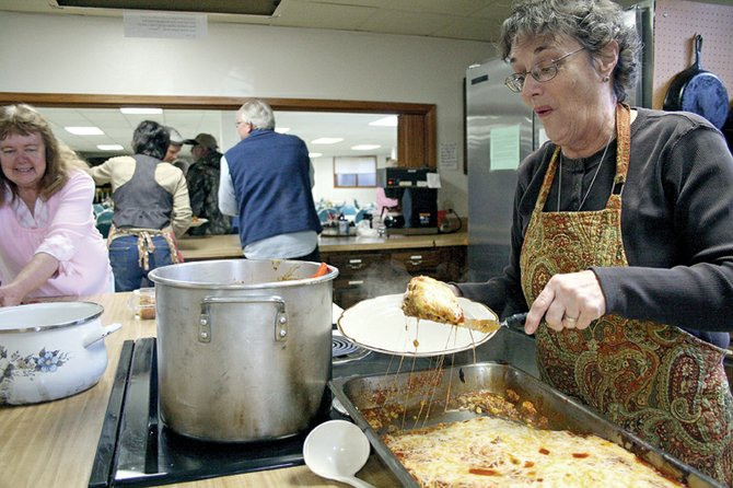 Susan Domer, a volunteer at St. Michael's Kitchen, serves taco pie during the kitchen's regular free lunch Tuesday. The kitchen recently received 2,650 pounds of food donations from employees of The Memorial Hospital.