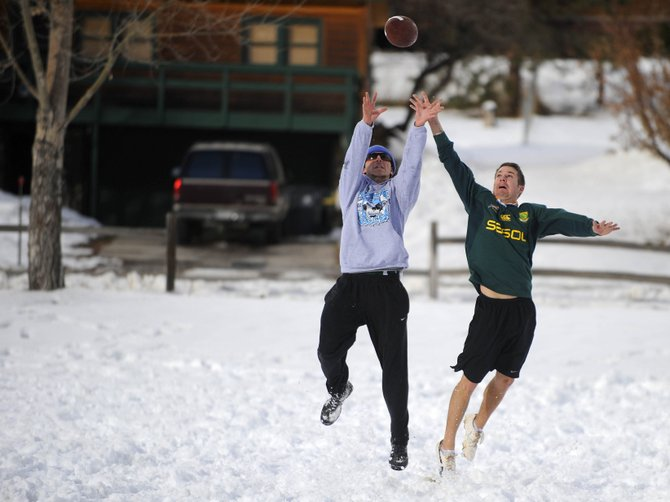 Aaron Gardner, right, and Steve Losack play football Sunday on a snow-covered field in front of Steamboat Springs High School. Snow is in the forecast through Wednesday.