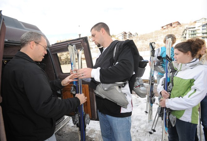 Kent Nanke, left, takes a pair of skis from Brandon Nanke on Tuesday as the Iowa family loaded its van with rental equipment in preparation for todays Scholarship Day at Steamboat Ski Area. All proceeds from today go toward Steamboat Springs Winter Sports Club scholarships.