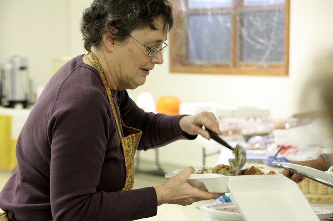 Susan Domer prepares a deliver box of food Thursday. St. Michael's Kitchen delivered Thanksgiving meals to community members, and hosted an open dinner at the church.